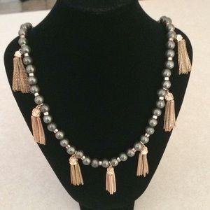 Kendra Scott pearl shaped stone with gold tassels.